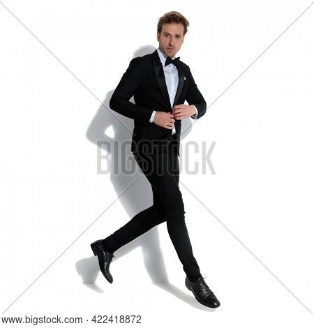 young handsome businessman jumping while adjusting his tuxedo and looking at the camera