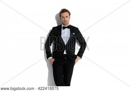 sexy businessman leaning on the wall with his hands in pockets in a fashion pose