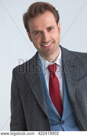 portrait of a young handsome businessman smiling at the camera and wearing a nice suit