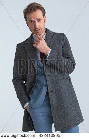 sexy businessman sensually touching his chin, looking at the camera and sticking one hand in pocket