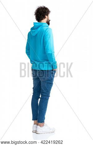 full body picture of unshaved young guy holding hands in pockets and waiting in line while standing against white background in studio