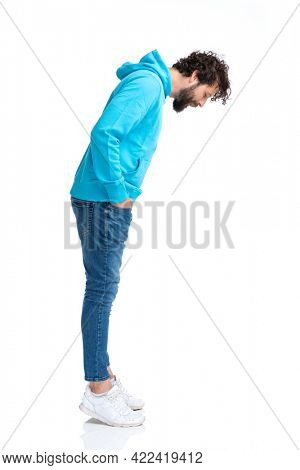 side view of handsome young man with long beard holding hands in pockets and looking down while waiting in line on white background in studio