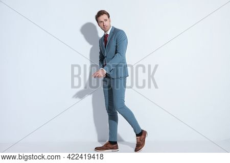 side view of sexy young man in blue suit looking to side and holding arm in a fashion pose while walking and posing against grey background