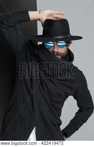 cool gypsy fashion model with sunglasses holding hand on hat in a fashion manner, being mysterious and hiding himself on black and gray background