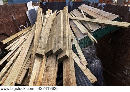Planks Of Unwanted Timber And Pallets Thrown Into A Dumpster At A House Construction Site