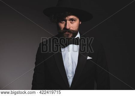portrait of a young handsome businessman looking at the camera in a cool tuxedo with black hat and bowtie