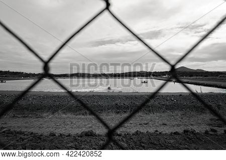 Looking Through A Wire Fence To A Prawn Aquaculture Farm With Aerated Pond, Rendered In Monotone