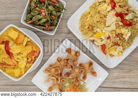 Full Feast Of Spicy Thai Food On The Wooden Table With The Featured Dish Being The Star Shaped Wonto