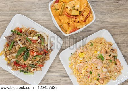 Full Feast Of Spicy Thai Food On The Wooden Table With The Featured Dish Being The Pineapple Curry.