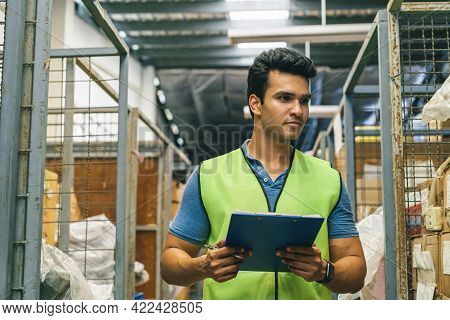 20s Indian Distribution Shipping Depot Worker Walking And Check Inventory. Male Worker In Working Un