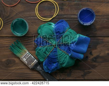 Coloring Clothes In The Style Of Tie Dye With Blue-green Color. Staining Fabric In Tie Dye Style.