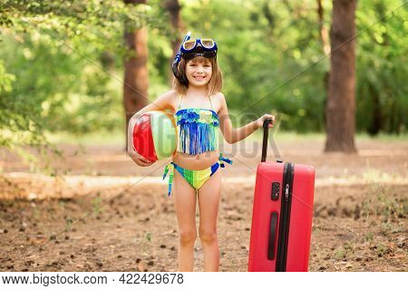 Enthusiastic Little Girl In Swimsuit, Fins And Swimming Mask With Swimming Ball Packed Suitcase, And