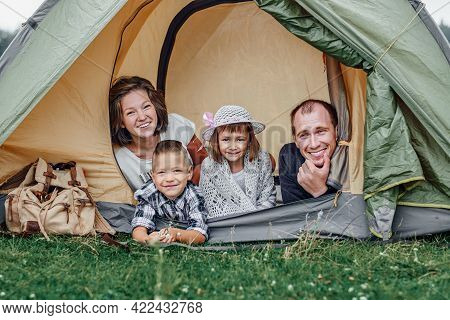 Family Parents And Two Children In Camp Tent. Happy Mother, Father, Son And Daughter On Summer Vacat