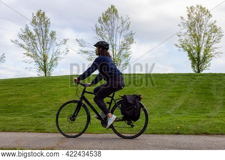 Adult Caucasian Woman Riding A Bicycle On A Path In A Modern City Park. Spring Evening. Taken In Haw