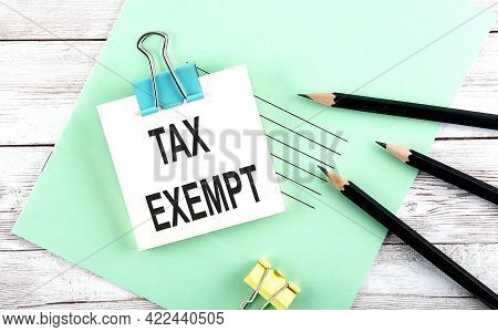 Text Tax Exempt On The Short Note With Pencils On Wooden Background