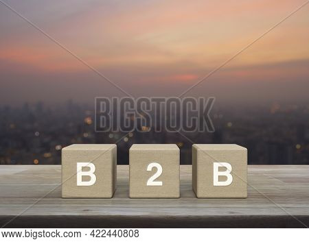 B2b Letter On Block Cubes On Wooden Table Over Blur Of Cityscape On Warm Light Sundown, Business To