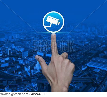 Hand Pressing Cctv Camera Flat Icon Over Modern City Tower, Street, Expressway And Skyscraper, Techn
