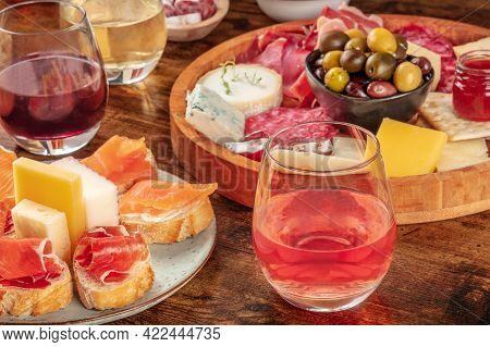 Wine, Sandwiches, Charcuterie And Cheese Board On A Rustic Wooden Background. Spanish Tapas Or Itali