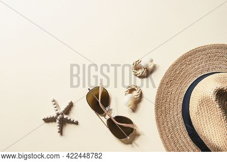 Flat Lay With Womens Summer Accessories On Neutral Background. Sunglasses, Straw Hat, Earrings And S