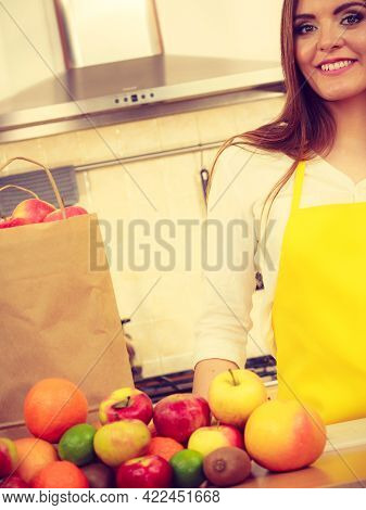 Woman Attractive Housewife In Kitchen With Grocery Shopping Bag, Many Fruits On Counter. Healthy Eat