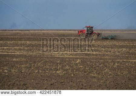 A Large Red Tractor With A Blue Plow Plows The Ground Before Planting Crops. Against The Background