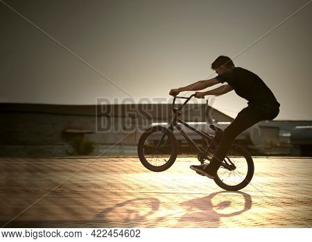teenager silhouette jump on a bicycle summer outdoors