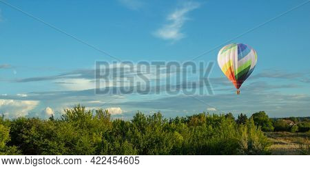 Balloons fly over the green fields, nature hills in summer