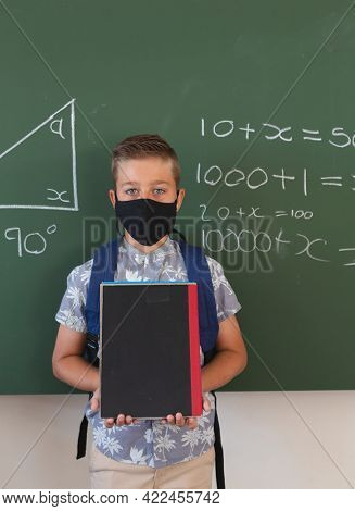 Portrait of caucasian boy in face mask standing at chalkboard with geometry on it holding books. childhood and education at elementary school during coronavirus covid19 pandemic.