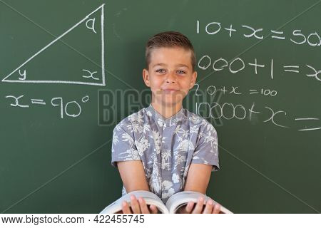Portrait of happy caucasian boy standing at chalkboard in maths lesson classroom holding schoolbook. childhood and education at elementary school.