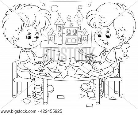 Happy Little Children Cutting Outlines And Figures From Paper With Scissors And Making A Funny Pictu