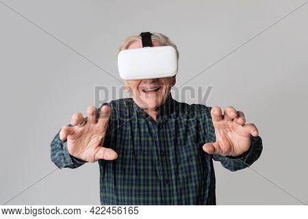 Cheerful senior man wearing virtual reality goggles