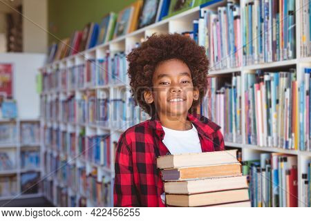 Smiling african american schoolboy carrying stack of books in school library. childhood and education at elementary school.