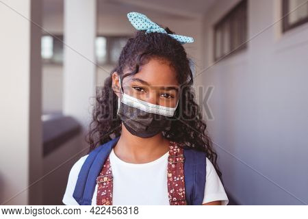 Portrait of african american schoolgirl in face mask standing in school corridor. childhood and education at elementary school during coronavirus covid19 pandemic.