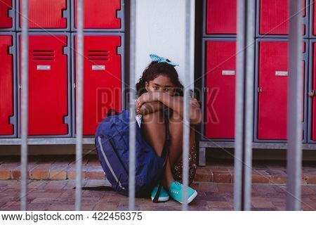 Unhappy african american schoolgirl sitting by lockers in school corridor with schoolbag. childhood and education at elementary school.