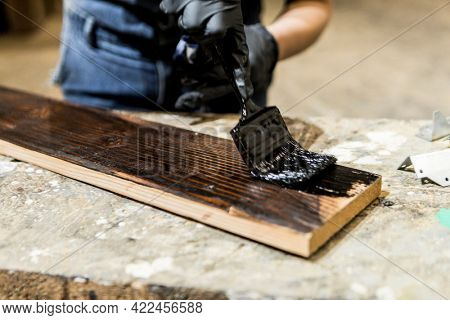 Female carpenter coating lumber with lacquer