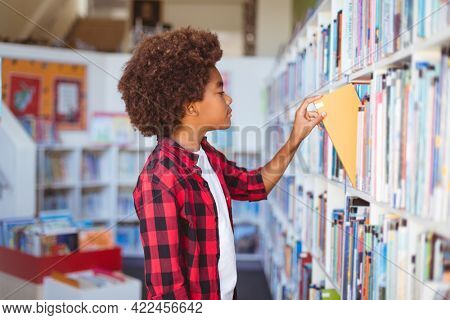Happy african american schoolboy taking book from shelf in school library. childhood and education at elementary school.