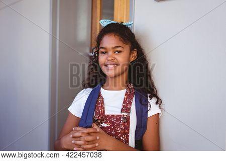 Portrait of smiling african american schoolgirl standing in school corridor wearing schoolbag. childhood and education at elementary school.