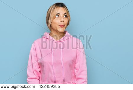 Young caucasian woman wearing casual sweatshirt smiling looking to the side and staring away thinking.