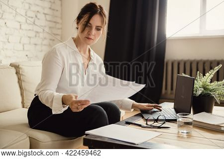 Middle aged business woman working at home with documents using laptop