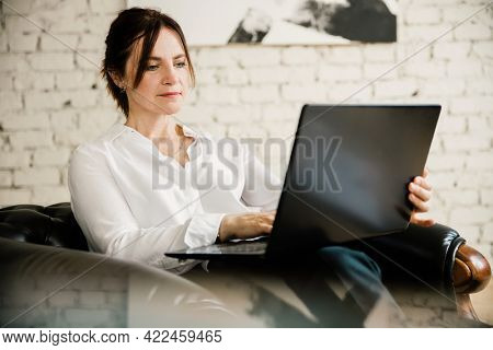 Middle aged business woman working at home using laptop