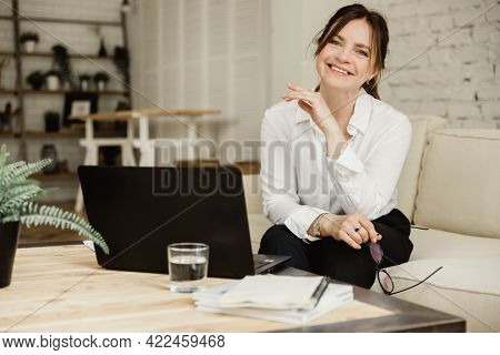 Middle aged business woman working at home using laptop, smiling and looking at the camera