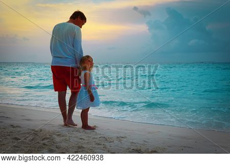 Father And Happy Little Daughter Walking On Beach At Sunset
