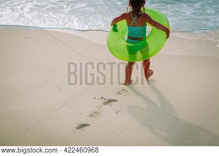Little Girl Go Swim On Beach Leaving Footprints In Sand