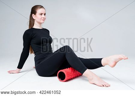 Attractive Young Girl Trainer In A Black Sweater And Leggis Does Exercises To Strengthen The Muscles