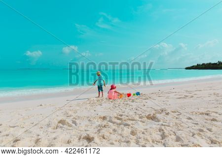 Happy Boy And Girl Play With Sand On Beach