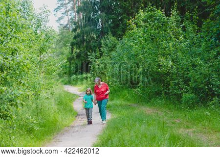 Happy Senior Grandmother With Granddaughter Walk In Nature