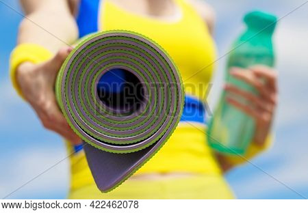 Fitness Girl With Yoga Mat Over Sky Background. Woman In Sports Wear Is Holding A Yoga Mat And A Bot