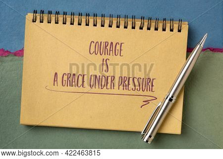 courage is a grace under pressure - inspirational handwriting in a spiral notebook against abstract paper landscape