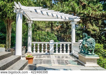 Gazebo With Old Bronze Statue Of Cupid & Lion. Blooming Plants All Around. Shot In City Park Of Aiva