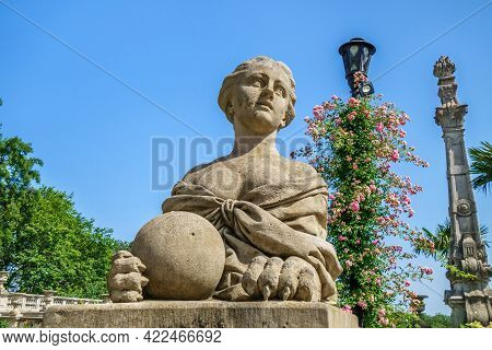 Sphinx With Female Head Holding Ball. Street Light With Flowers And Column Are On Background. All Of